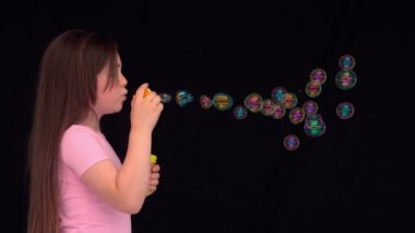 Side view of a little girl making bubbles — Stock Video