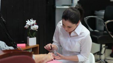 Beautician varnishing toenails — Stock Video
