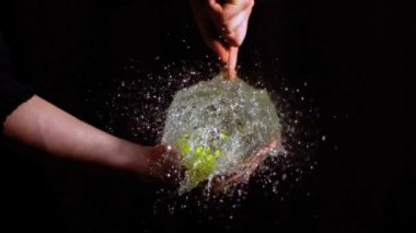 Man bursting green water balloon — Stock Video