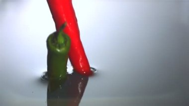Chili peppers falling in water — Stock Video