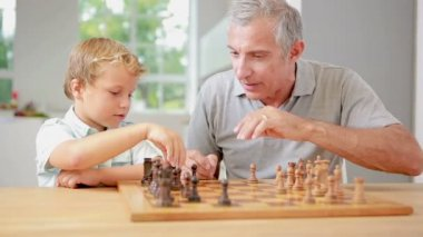 Child learning to play chess with his grandpa — Stock Video
