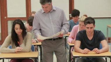 Teacher giving out tests — Stock Video