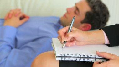 Muž leží na pohovce s terapeutem poznámky — Stock video