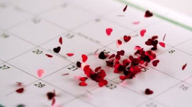 Pink heart confetti falling on calendar — Stockvideo