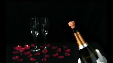 Champagne cork popping in front of two flutes — Stock Video