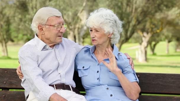 Un par de viejos en un banco hablando — Vídeo de stock
