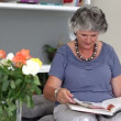 Woman reading a book on the couch — Stock Video