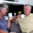 Mature couple chatting  together with a cup of coffee — Stock Video