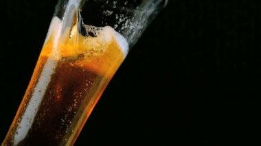 Beer pouring into glass on black background — Stock Video
