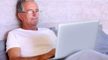 Elderly man using laptop in bed — Stock Video
