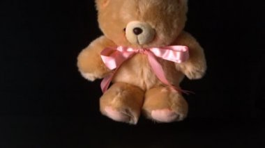 Teddy bear with pink ribbon falling on black background — Stock Video