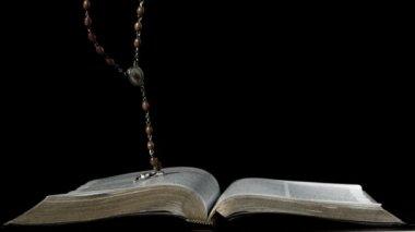 Rosenkranz fallen auf Öffnen Sie Bibel auf schwarzem Hintergrund — Stockvideo