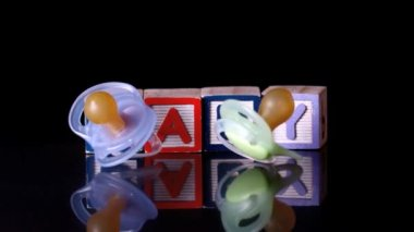 Pacifiers falling in front of blocks spelling baby — Stock Video