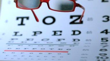 Red glasses falling on eye test — Stock Video