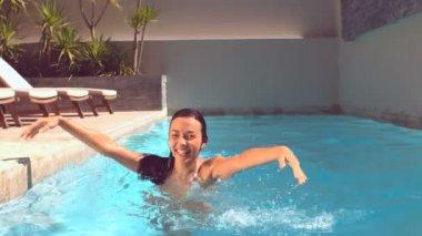 女性は立っているとプールの中で水しぶき — ストックビデオ