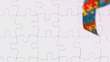 Autism ribbon falling onto jigsaw surface — Stock Video