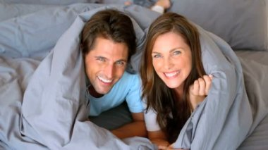Couple having fun wrapped in duvet — Stock Video
