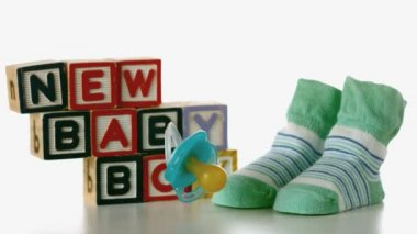 Blue soother falling besides slippers and baby blocks — Stock Video