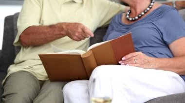Mature couple laughing while looking at a book — Stock Video