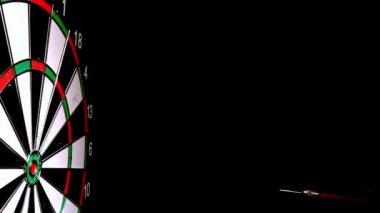 Dart hitting the bulls eye side view on black background — Stock Video