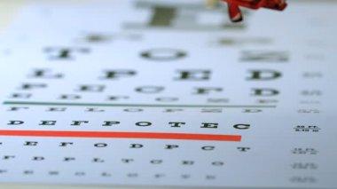 Reading glasses falling onto eye test — Stock Video