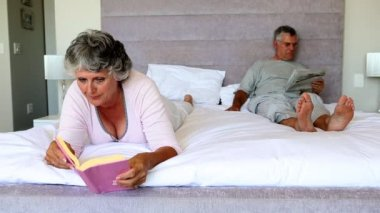Mature couple reading in the bedroom — Stock Video