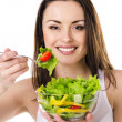 Beautiful young girl eats salad — Stock Photo