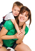 Beautiful mom giving her son a piggyback ride — Stock Photo