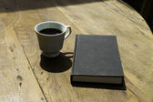 Black Book and Black Coffee on Wooden Table — Stock Photo