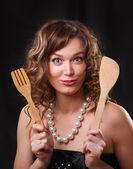 Ritratto di una giovane e bella donna con merce di cucina su un oscuro — Foto Stock