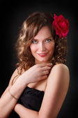 Portrait of smiling beautiful young woman with Red flower — Stock Photo