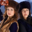 Two young womin fur hats in winter forest — Stock Photo #22272299