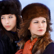 Two young women in fur hats in winter forest — Stock Photo #22272637