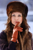 Young beaytiful women in fur hats in winter forest — Stock Photo