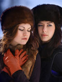 Two young woman in fur hats in winter forest — Stock Photo