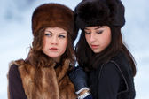 Two young women in fur hats in winter forest — Stock Photo
