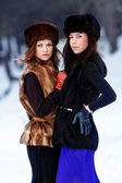 Two young beautiful women in fur hats in winter forest — Stock Photo