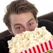 Man looking up from the popcorn - Stock Photo