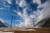 Power poles line towers in natural landscape — Stock Photo