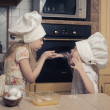 Kids cooking products, including childrens aprons, chef outfits, kitchen utensils. - Stock Photo