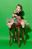 Girl is in studio on green background in different outfit — Stok fotoğraf
