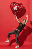 Girl tries to fly on the big balloon on the red background. — Stockfoto