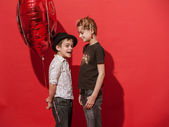 Girl and boy with big hearty red balloon on the red background. — Stock Photo