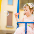 Sweet little girl in pink dress on a swing. — Stock Photo