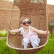 Little girl in sunglasses and a pink dress shakes on a swing. — Stock Photo