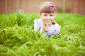 Little girl lies on grass on belly. — Stock Photo