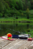 Fishing supplies on a table near a lake — Stock Photo