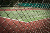 Tennis court in metal fence — Stock Photo