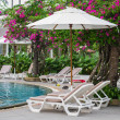 Stock Photo: Couches with umbrellas around pool