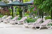 Couches with umbrellas in the garden — Stock Photo